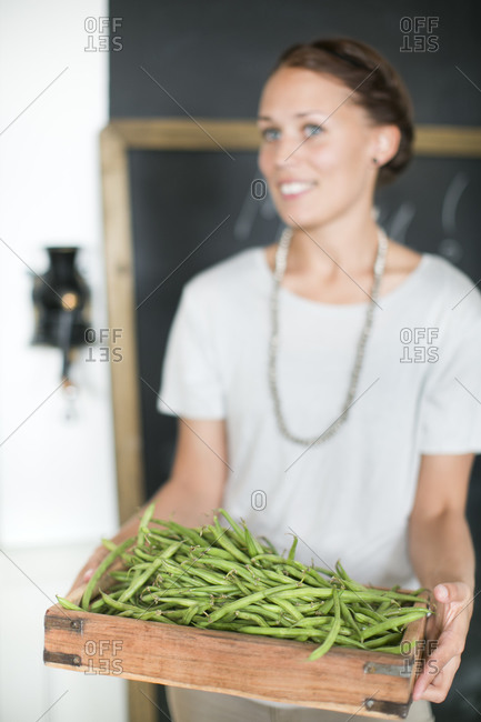 Woman holding green beans in wooden box