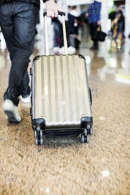 Person pulling suitcase, low section
