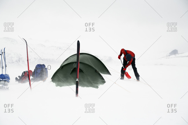 Person digging in snow at camping, Sarek national park, Lapland, Sweden