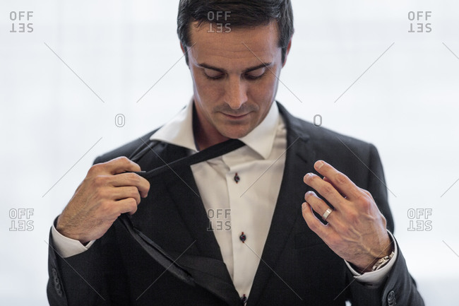 Businessman taking off tie, Stockholm, Sweden