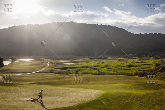 A worker tends to a golf course at sunset in Dalat, Vietnam.