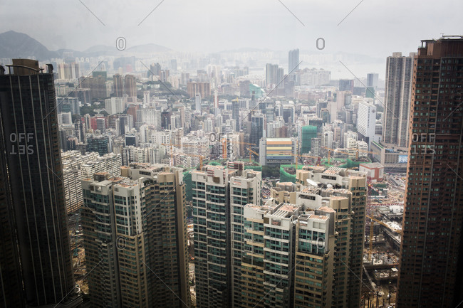 A cityscape of Hong Kong island, with the harbor, buildings, and mountains beyond.