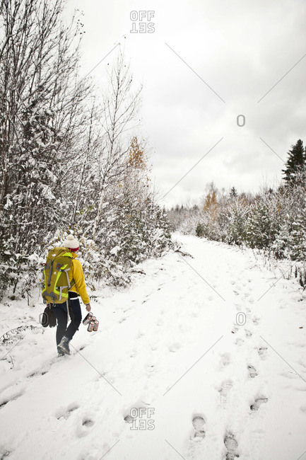 A person hikes through the first snowfall in the Maine