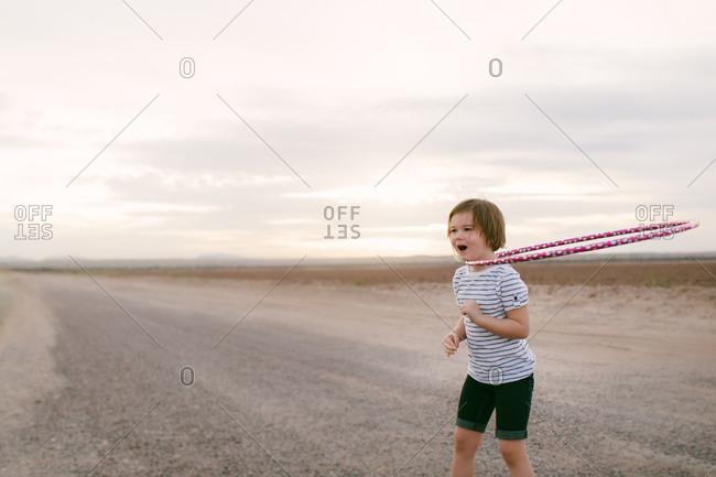 Little girl hula hooping on an empty road