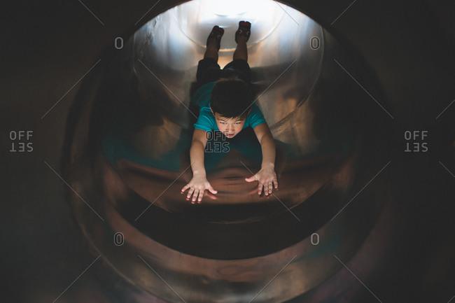 Little boy sliding down a covered slide