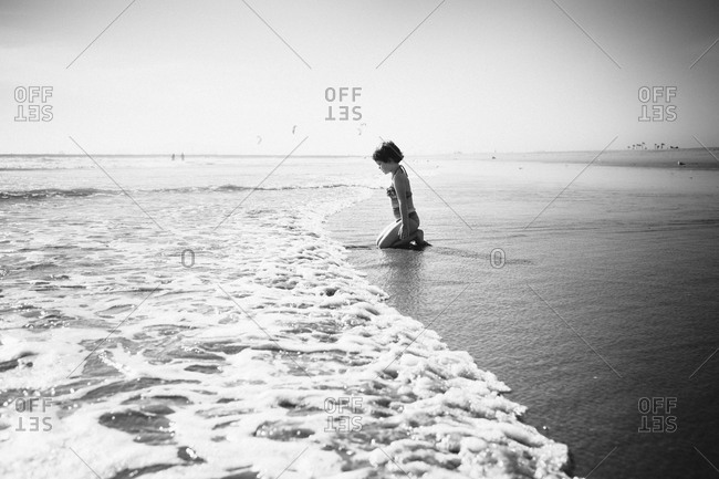 Little girl kneeling on beach watching the waves