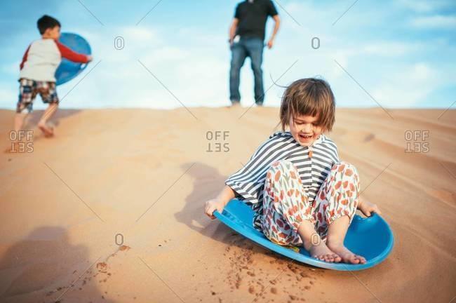 Little girl sledding down a sand dune