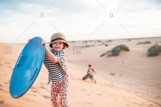 Kids running up a sand dune
