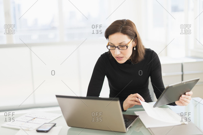 Businesswoman working on laptop and digital tablet