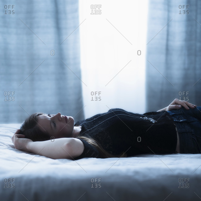 Portrait of beautiful woman lying down on bed