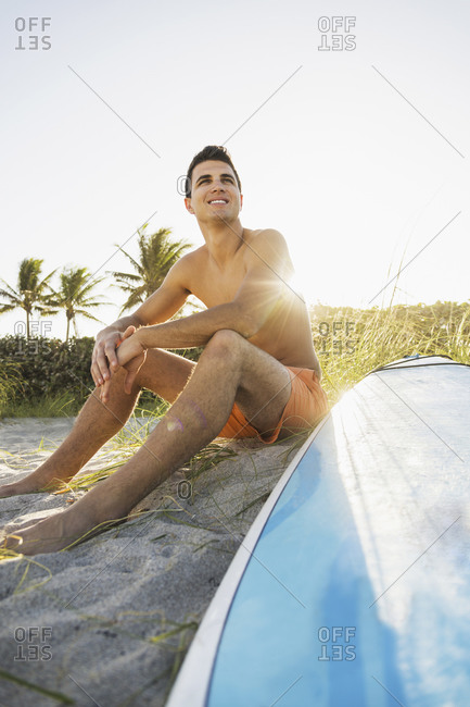 Young man sitting on beach with surfboard