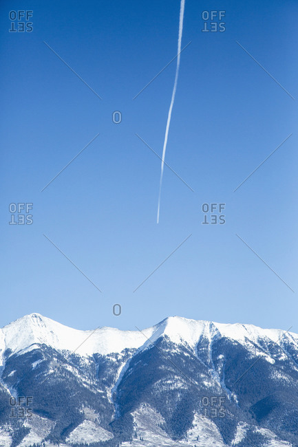 Vapor trail on clear sky above mountains