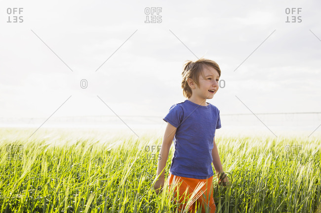 Boy standing in grass and looking away