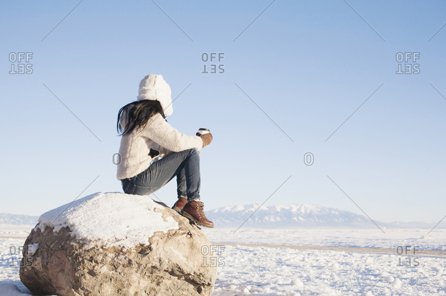 Woman sitting on rock with cup in winter