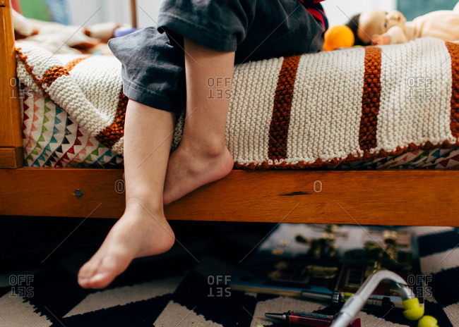 Child sitting on edge of bed