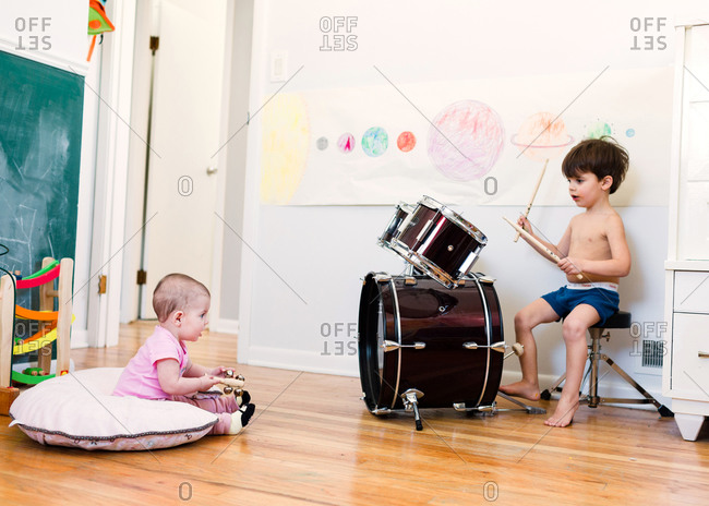 Boy plays drums while sister plays bells