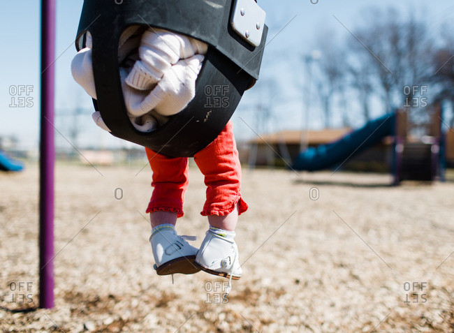 Low angle view of baby girl at playground playing on swing