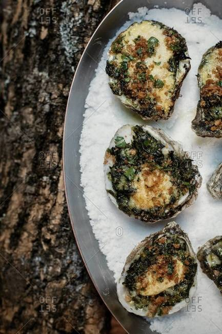 Oysters Rockefeller served on a tray of salt