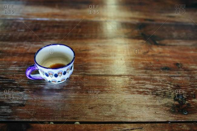 Tin-glazed cup on a wooden table