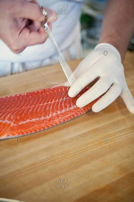 Chef removing fish bones from a salmon filet
