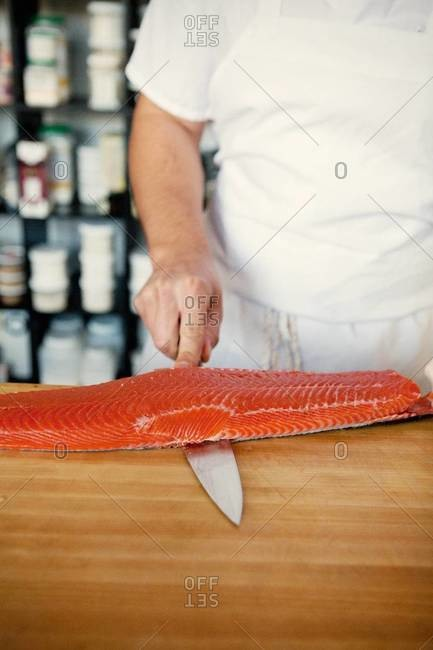 Chef removing the skin of a salmon filet