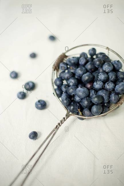 Close up of blueberries in a strainer spoon