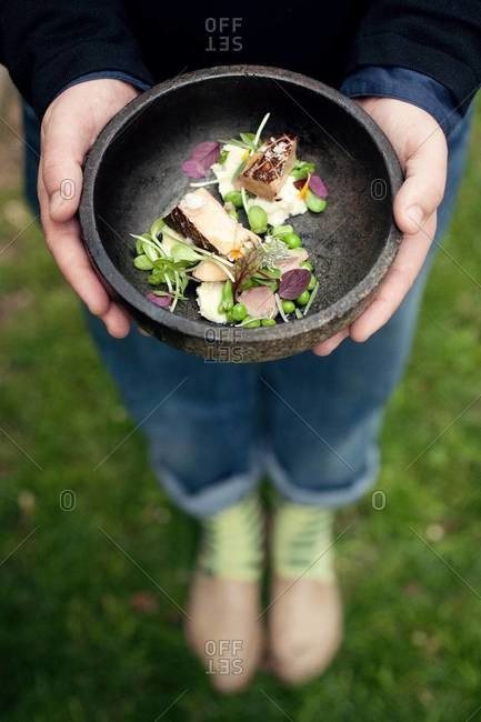 Person holding a dish of foie gras and pea tendrils