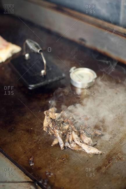 Sliced up steak roasting on a griddle stove