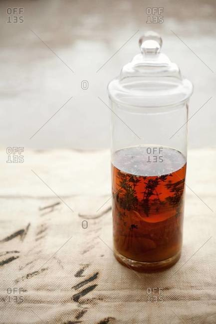 Close up of a glass container with honey infused bourbon