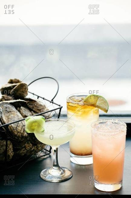 Gimlet cocktails with a basket of fresh oysters