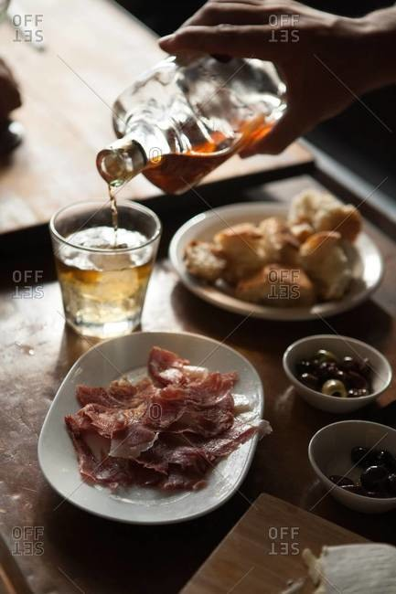 Appetizing dry-cured ham, olives, bread and cheese