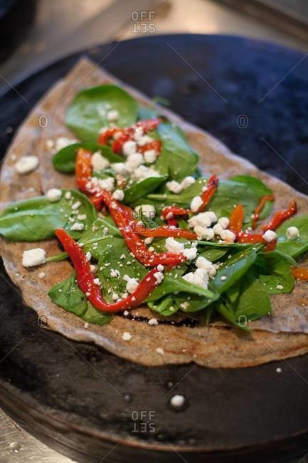 Galette with spinach, pepper and cheese topping