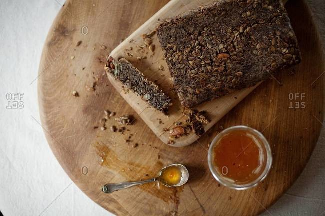 Nut and seed bread with jam on cutting board