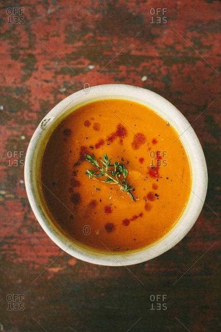 Carrot creme soup with thyme topping served in bowl