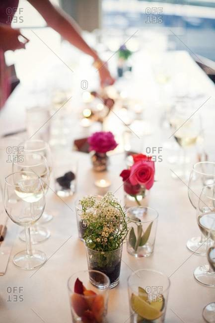 Long table with different glasses and cut flowers