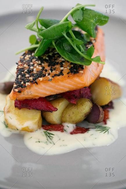 Salmon fillet with fingerling potatoes, grilled beetroot, dill sauce and green leaves