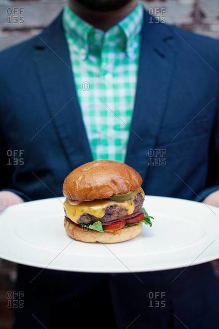 Mid section view of man holding hamburger on plate