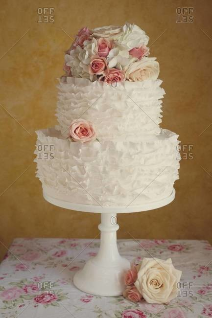 Tiered wedding cake decorated with roses on cake stand