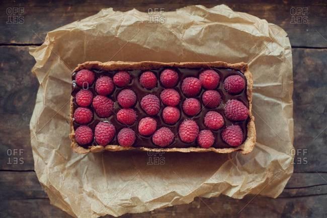 Dark chocolate raspberry tart served on parchment