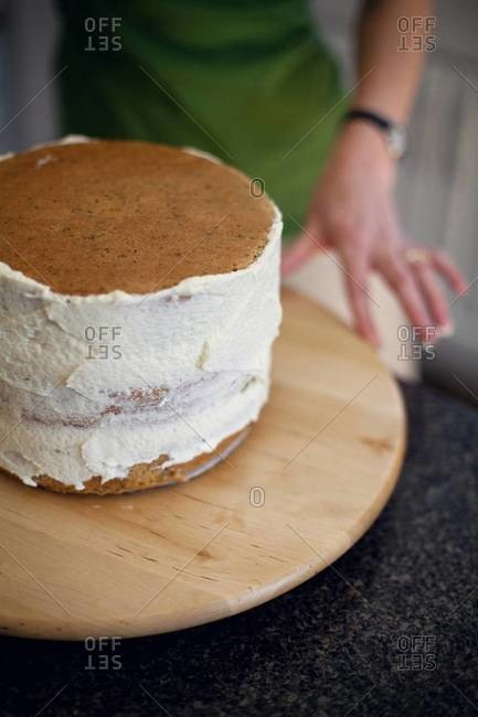 Glazing a cake with honey vanilla buttercream