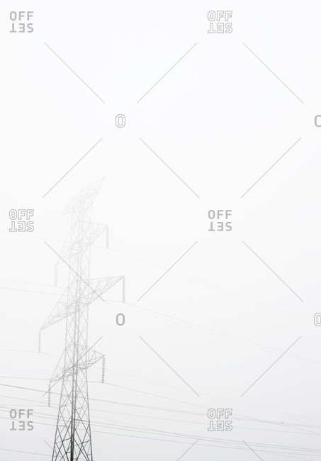 Electrical tower disappears on a foggy day
