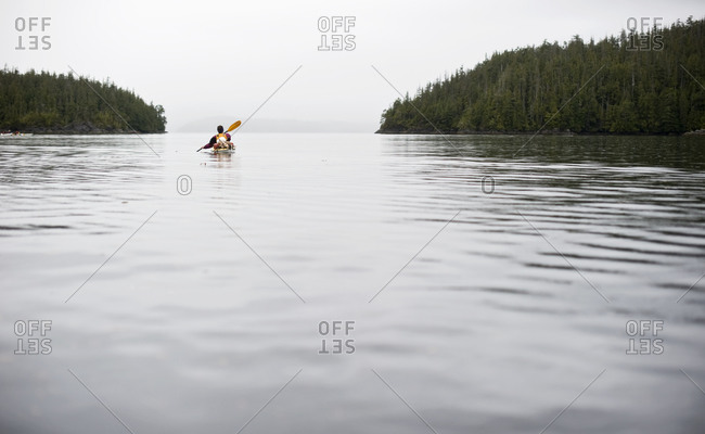A kayaker paddles off into the horizon