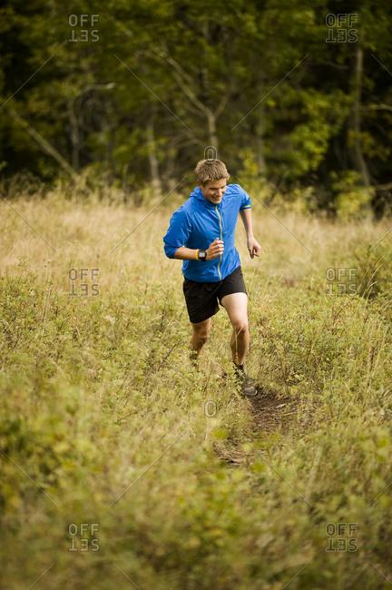 Man runs through a lush field