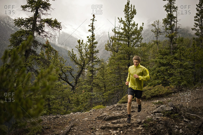 Athletic young man runs on a mountain trail