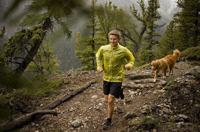 Athletic young man runs on a mountain trail with a happy dog
