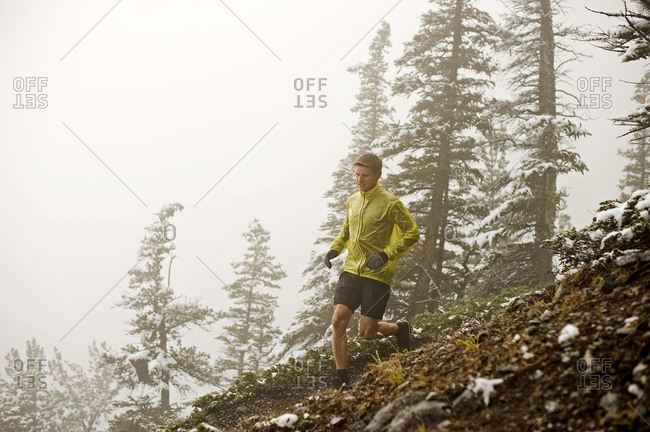 Athletic young man down a sloping mountain trail