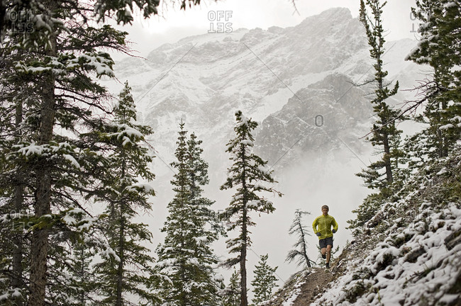 Athletic young man running along steep mountain trail