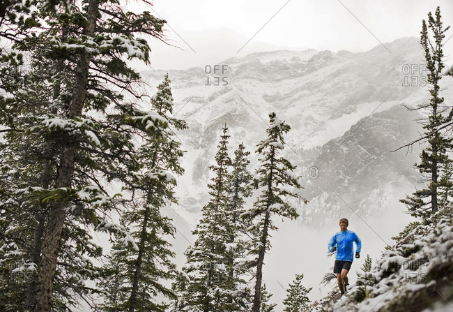 Athletic young man running along mountain\'s edge