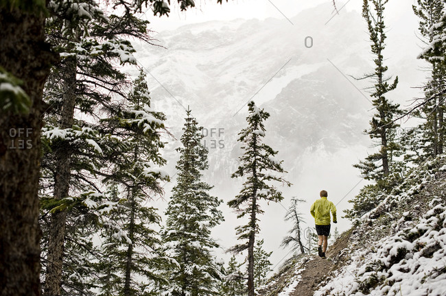 Athletic young man running on steep mountain incline