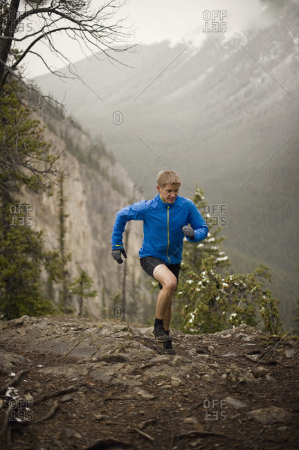 Athletic young man running up a steep slope